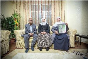 إيمنين تحمل صورة ابنها ماهر والى جوارها زين وعمر («الشرق الأوسط»)